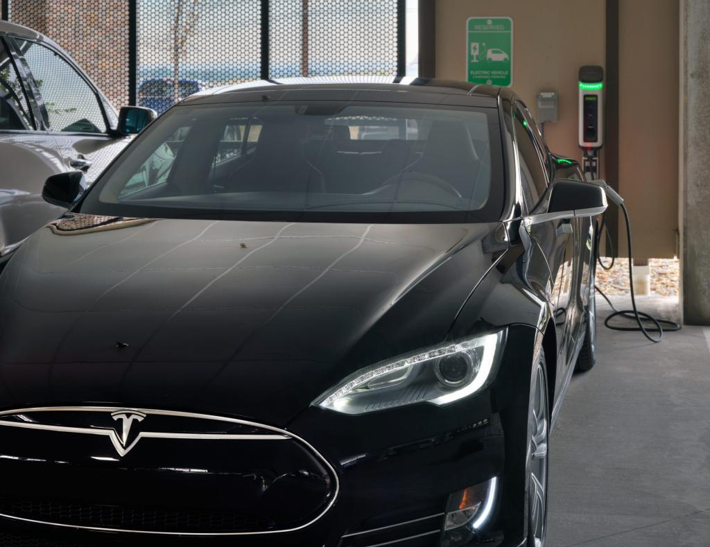 Tesla using electric vehicle charging station