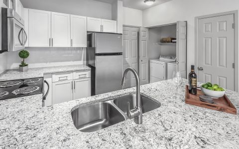 Kitchen with quartz countertops and stainless steel appliances at Camden Lakeway Apartments in Lakewood, Colorado