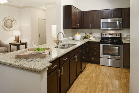 Kitchen with Granite Countertops and Stainless Steel Appliances at Camden Breakers Apartments in Corpus Christi, TX