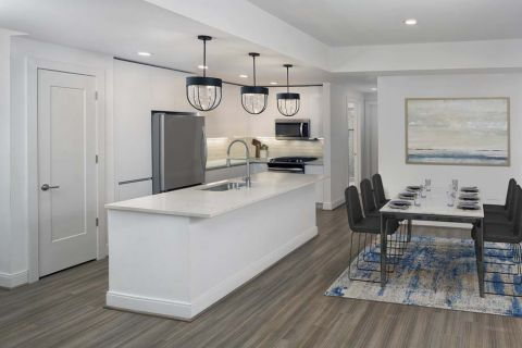 White contemporary kitchen and dining room at Camden Buckhead apartments in Atlanta, GA