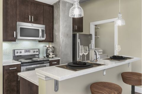 Kitchen with Island and Full-Size Washer and Dryer in Laundry Room at Camden Cotton Mills Apartments in Charlotte, NC