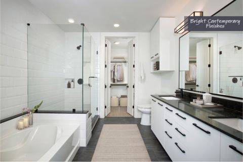 Bathroom with Glass Enclosed Shower, Soaking Bathtub, and Walk-In Closet in Bright Contemporary Finish Scheme at Camden Downtown Houston Apartments in Houston, Texas
