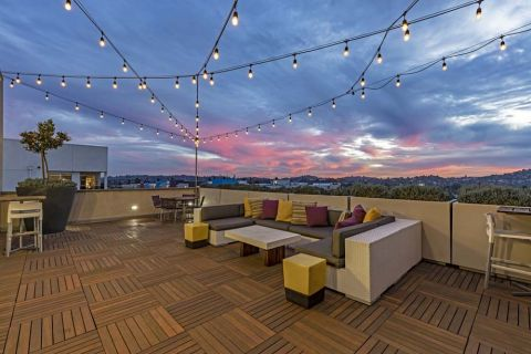 Outdoor Sky Deck Lounge with Sunset and String Lights at Camden Glendale Apartments in Glendale, CA
