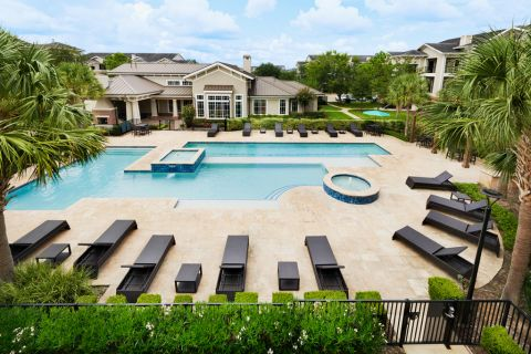 Pool with lounge chairs at Camden Grand Harbor Apartments in Katy, TX