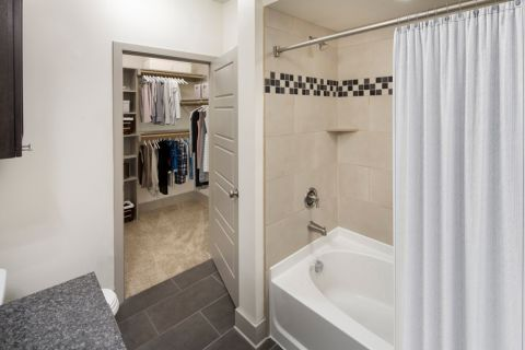Bathroom with tub and large closet at Camden Henderson Apartments in Dallas, TX