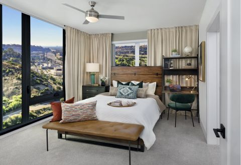 Bedroom with floor-to-ceiling windows and ceiling fan at Camden Hillcrest Apartments in San Diego, CA