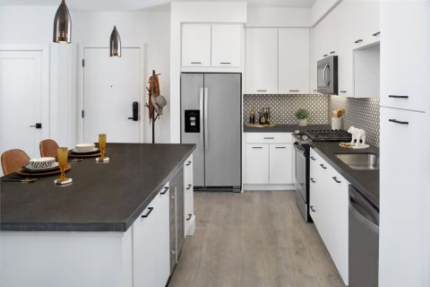 Kitchen with stainless steel appliances and island at Camden Hillcrest Apartments in San Diego, CA