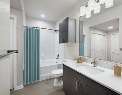 Bathroom with Quartz Countertops and Wood-Look Flooring at Camden Huntingdon Apartments in Austin, TX
