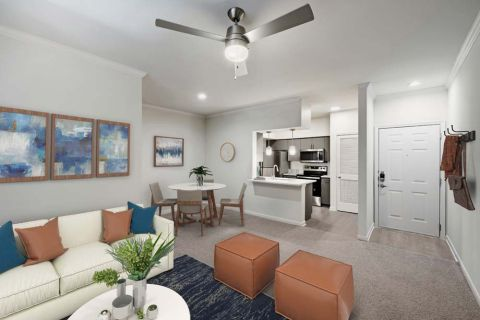 Living, Dining, and Kitchen with Carpet Flooring and Ceiling Fan at Camden Huntingdon Apartments in Austin, TX