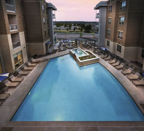 Resort-Style Swimming Pool and Hot Tub at Sunset at Camden Lincoln Station Apartments in Lone Tree, CO