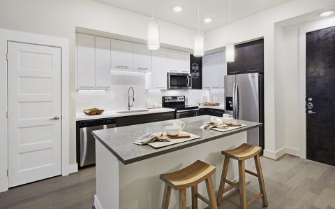 Model Kitchen with Quartz Countertops and Kitchen Island at Camden McGowen Station Apartments in Houston, TX