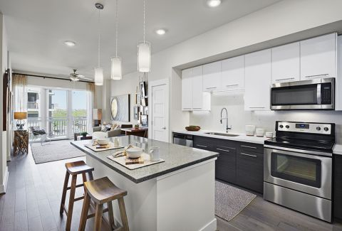 Open-Concept Kitchen and Living Room with Wood Plank Flooring at Camden McGowen Station Apartments in Houston, TX