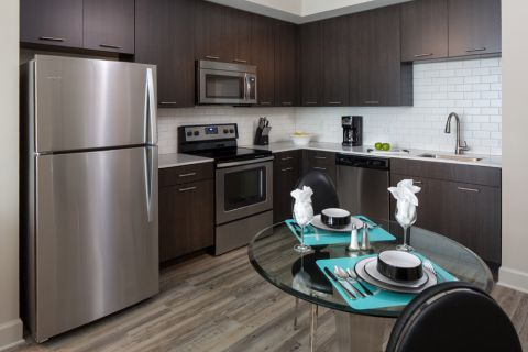 Kitchen with Quartz Countertops, Espresso Cabinetry and Stainless Steel Appliances at Camden North Quarter Apartments in Orlando, Florida