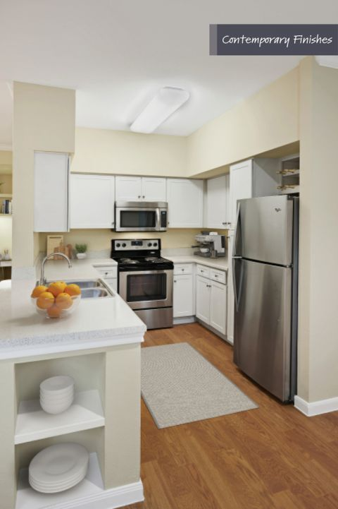 Kitchen with contemporary finishes and stainless steel appliances at Camden Oak Crest Apartments in Houston, TX