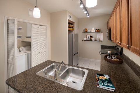 Kitchen and Laundry at Camden Panther Creek Apartments in Frisco, TX
