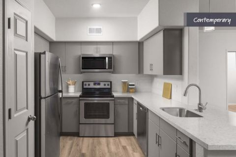 Kitchen with White Quartz Countertops, Stainless Steel Appliances and Gray Cabinetry at Camden Pecos Ranch Apartments in Chandler, AZ
