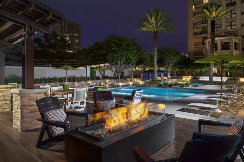 Outdoor Fire Pit with Lounge Seating at Camden Post Oak Apartments in Houston, TX