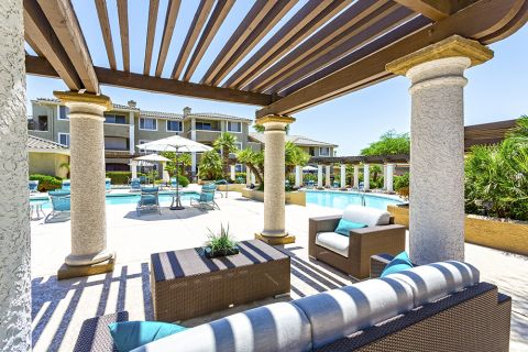 Poolside outdoor lounge with fireplace at Camden San Marcos Apartments in Scottsdale, AZ