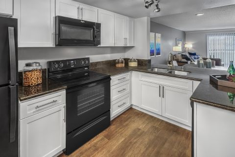 Kitchen with black and stainless steel appliances at Camden Sea Palms Apartments in Costa Mesa, CA