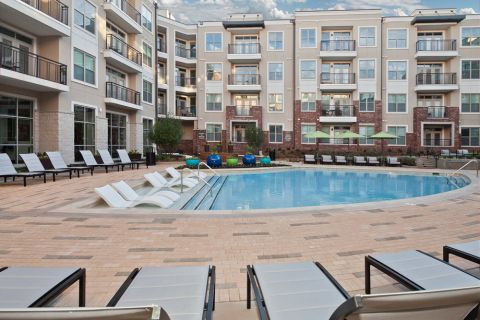 Swimming pool with lounge chairs at Camden Southline apartments in Charlotte, NC