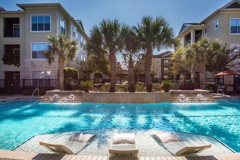 Swimming Pool with Lounge Chairs at Camden Spring Creek Apartments in Spring and The Woodlands, TX