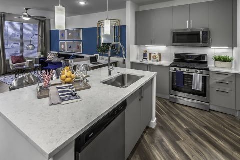 Open-Concept Kitchen with Large Island, Stainless Steel Appliances and Built-In Microwave at Camden Washingtonian Apartments in Gaithersburg, MD