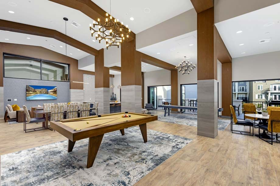 Resident Club Lounge with Billiards and Shuffleboard Tables and TV at Camden Harbor View Apartments in Long Beach, CA