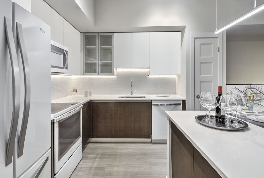 Kitchen with Quartz Countertops, Sleek White Cabinets at Camden NoMa Apartments in Washington, DC