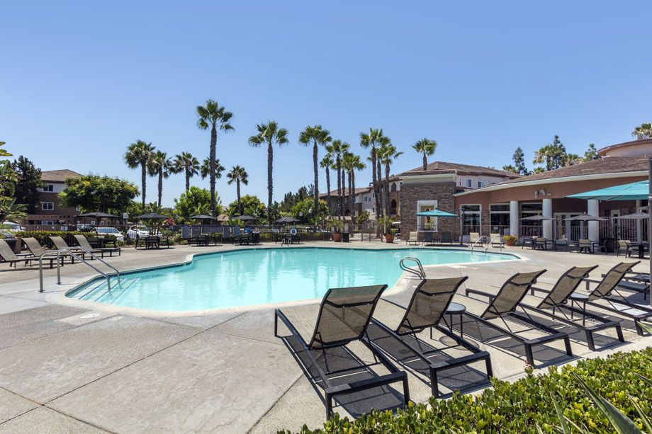 Resort-style swimming pool with lounge chairs at Camden Sierra at Otay Ranch apartments in Chula Vista, CA