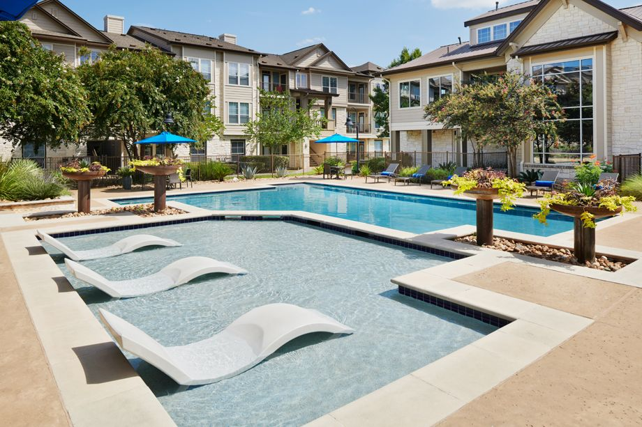 Swimming pool with lounge chairs at Camden Cedar Hills apartments in Austin, TX