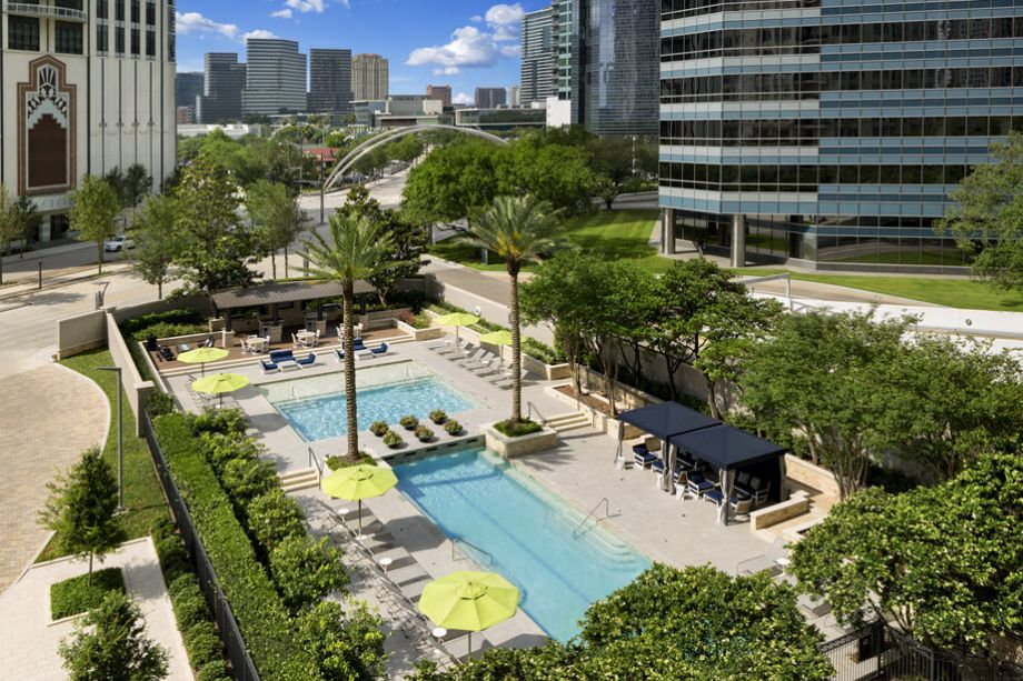 Pool with sundeck, cabanas, and outdoor dining area at Camden Post Oak High Rise Luxury Apartments