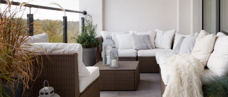 Decorated patio with white pillows, white cushions and a white blanket.