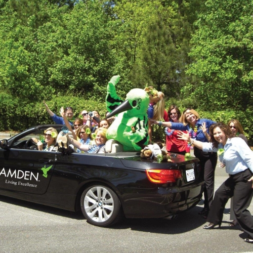 Camden's mascot, the Hummingbird, enjoying a ride in a convertible with other Camden employees