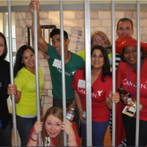 Camden employees pretending to be behind bars during a corporate event in Houston, Texas