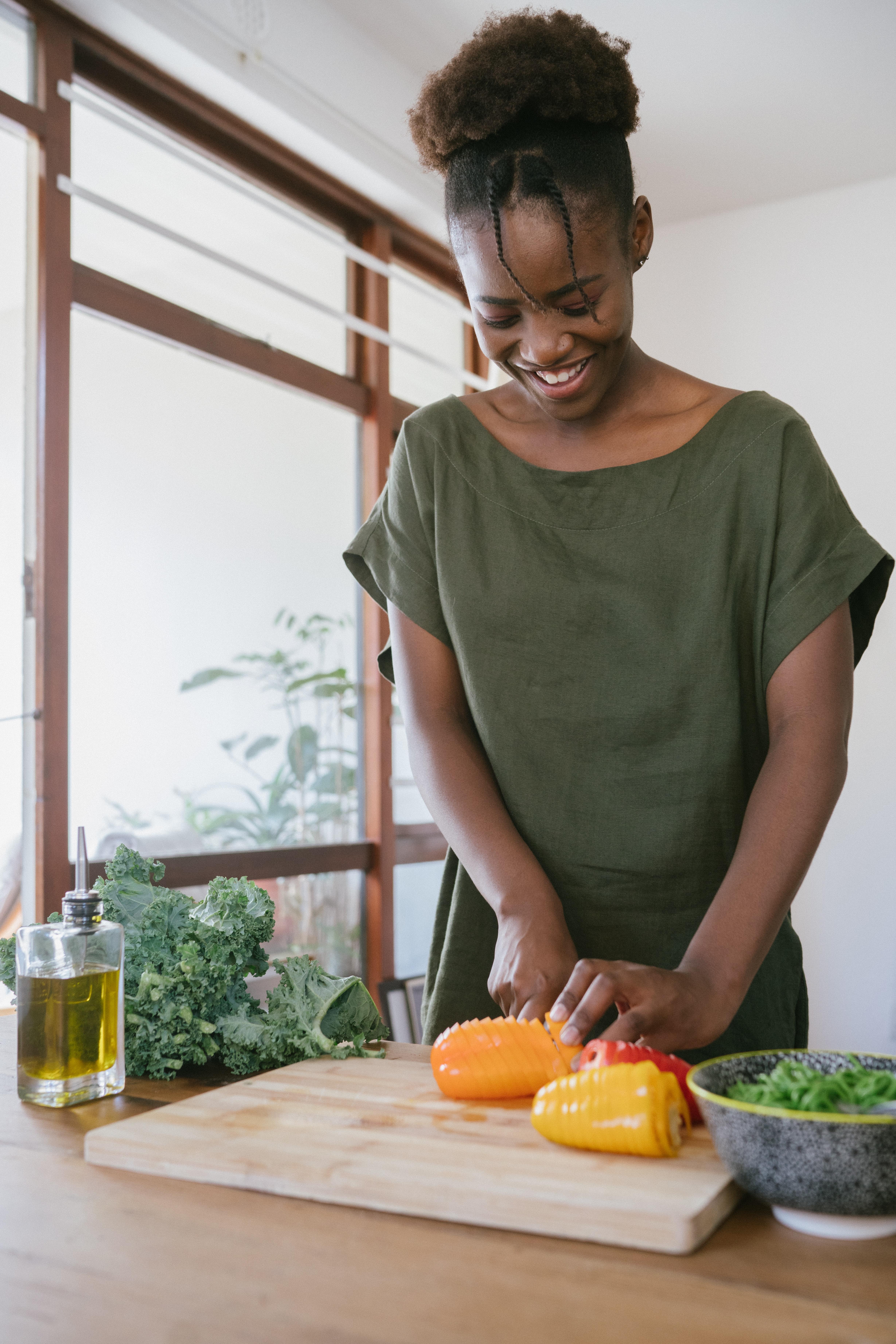 woman-in-green-tank-top-holding-orange-bell-pepper-3622643.jpg